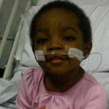little girl smiling at camera from hospital bed.