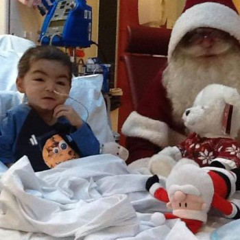 pictured is a little child, in a hospital bed, sat with Santa.
